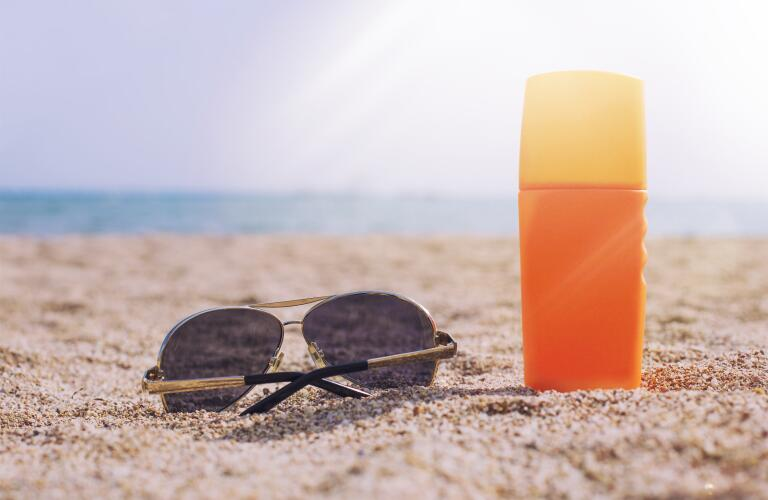 sunscreen-bottle-with-sunglasses-on-beach