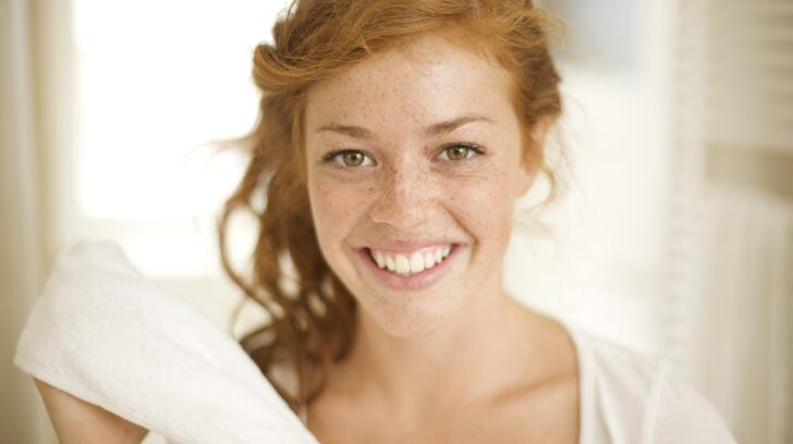 Close-up of young red-headed Caucasian woman with freckles smiling