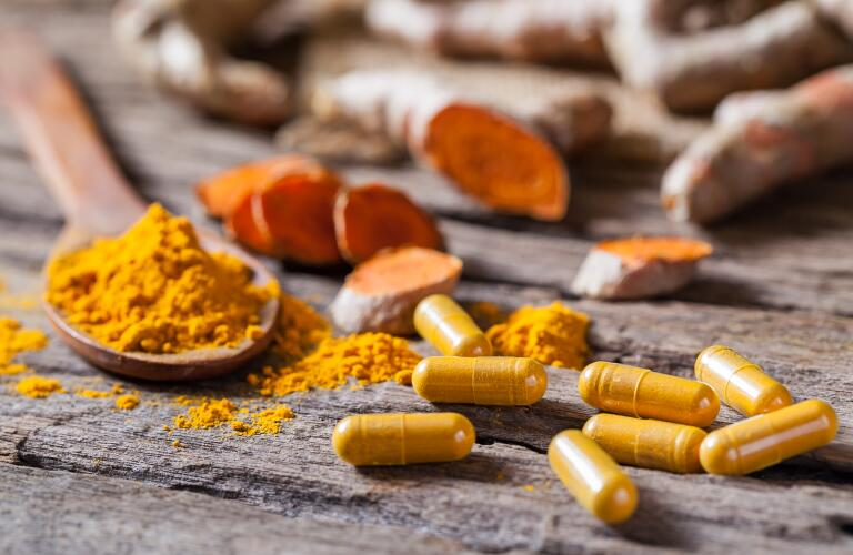 turmeric powder, turmeric capsule and turmeric root on wooden background