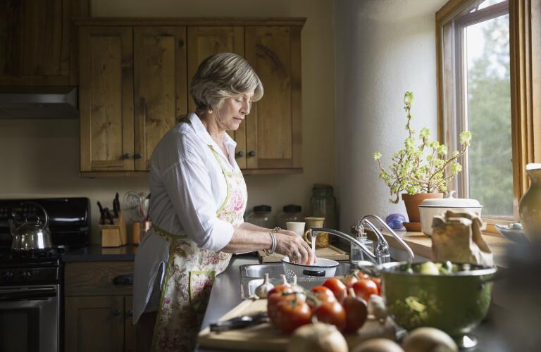 Senior woman washing vegetables at kitchen sink