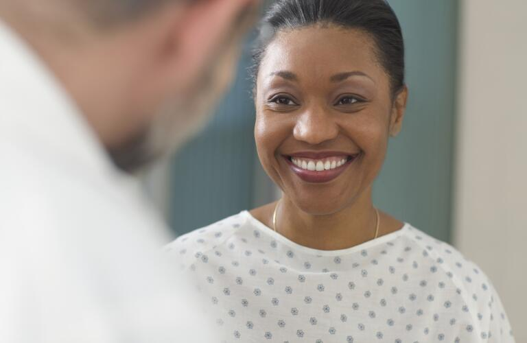 Close-up of African American female patient in hospital gown smiling at doctor