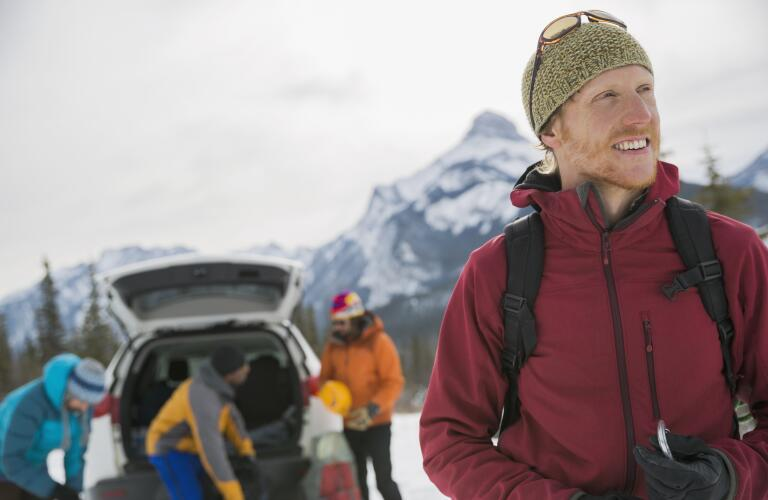 smiling man in winter weather ready for hike with friends