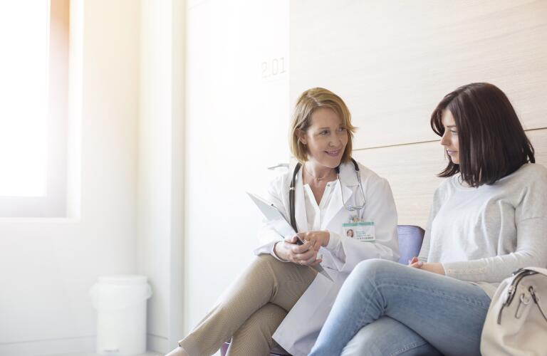 female doctor reviewing medical charts with female patient