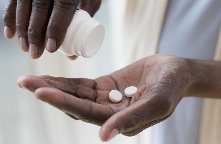 mature woman taking medication, round white pills