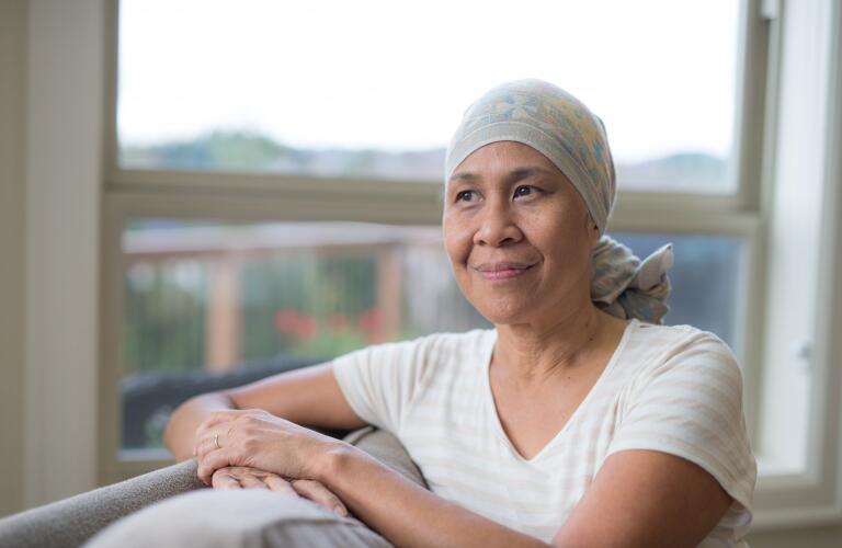 cancer patient sitting by window in head wrap