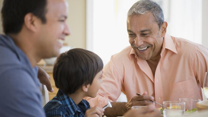 grandfather smiling at table with son and grandson