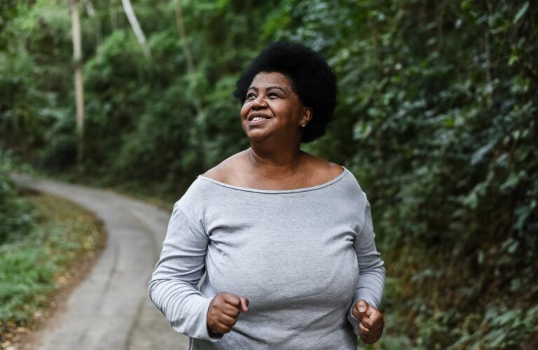 smiling African American woman walking or jogging through forest trail