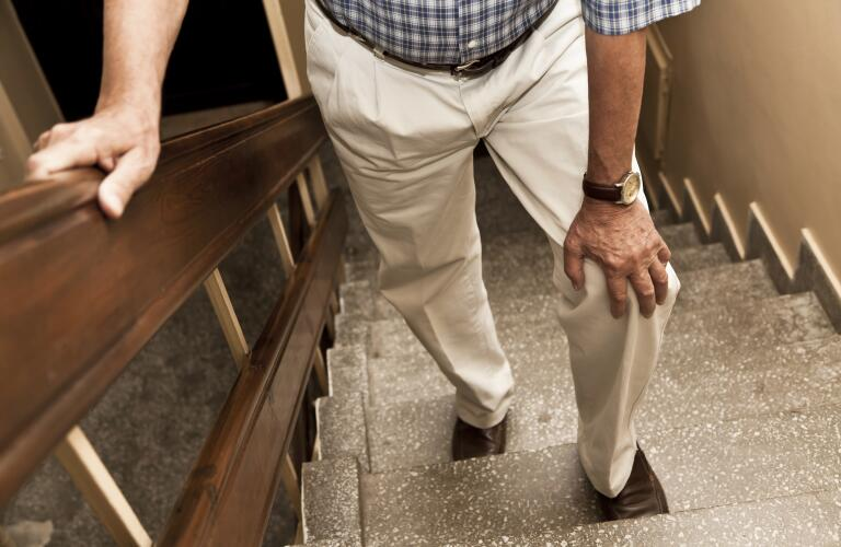 Unseen older man experience knee pain on stairs