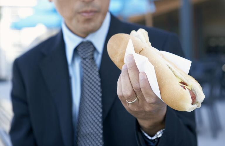 Unseen Caucasian businessman eating hot dog