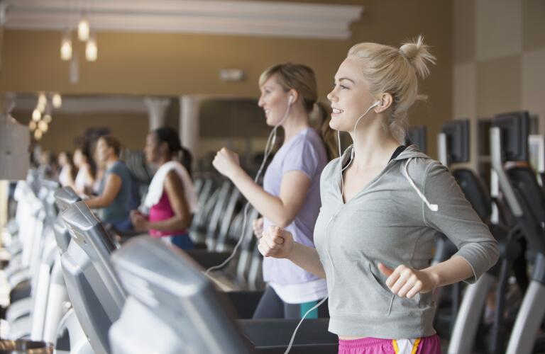 smiling blonde Caucasian female running on treadmill at gym wearing earbuds