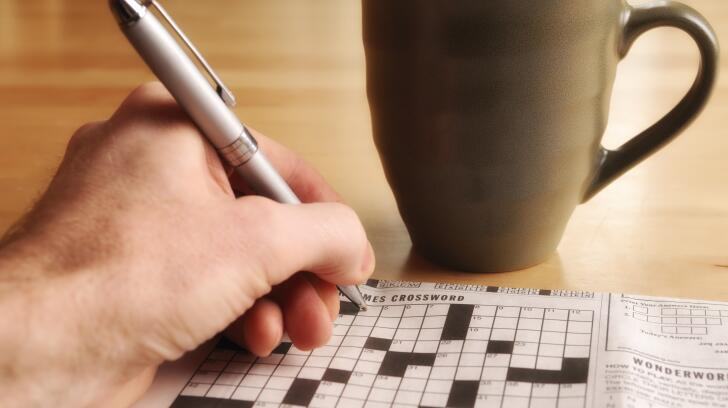 Close-up of man's hand doing crossword puzzle