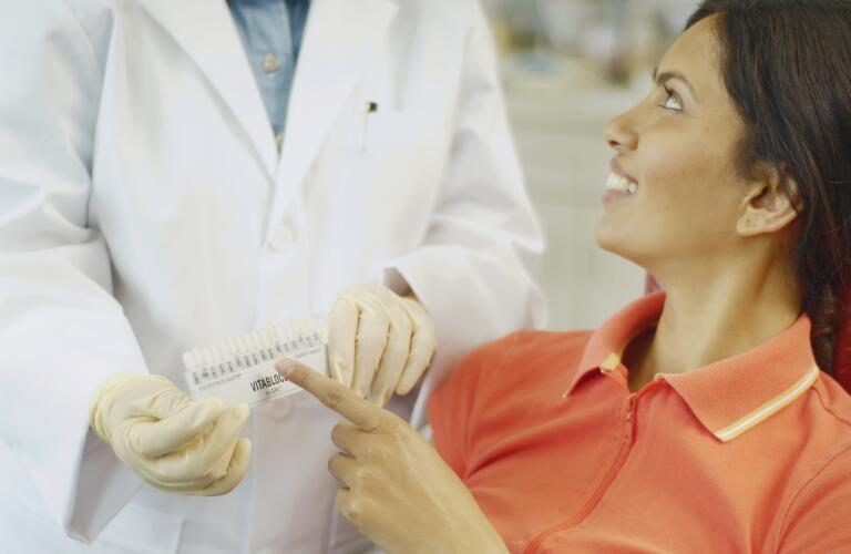 dental patient choosing tooth color sample from dentist