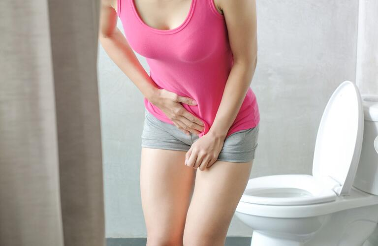 woman in bathroom pressing her hand to her pelvic area indicating pain or cramping