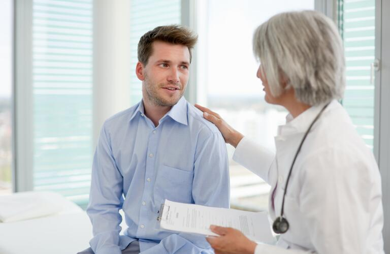 Doctor and young male patient discuss results