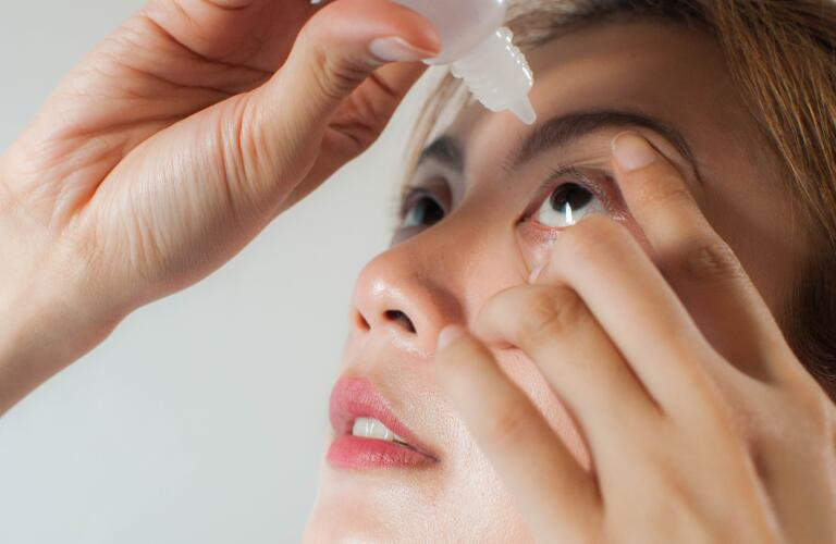 young woman applying medicine or saline drops in her eyes