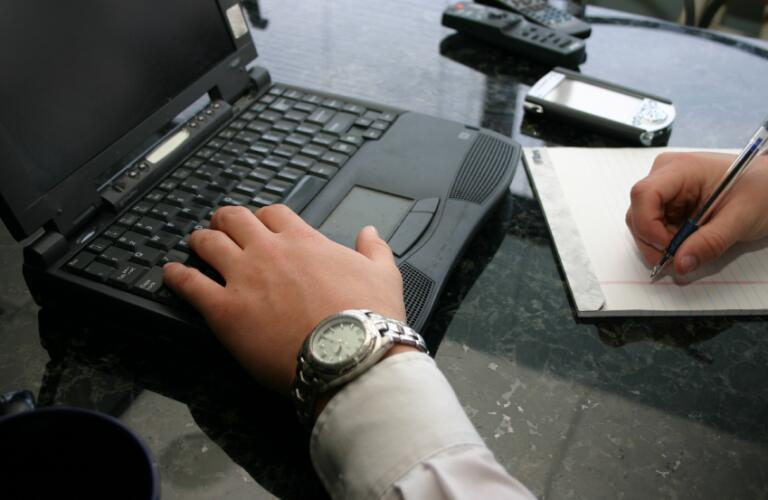 businessman typing and writing
