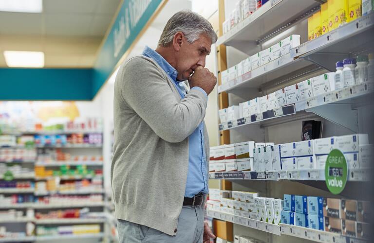 man with cough in pharmacy looking for medicine