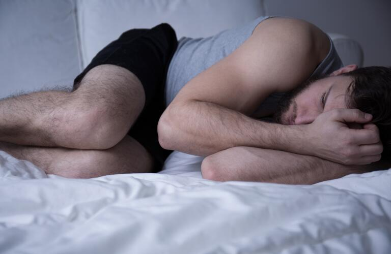 man-curled-up-in-bed-having-trouble-sleeping