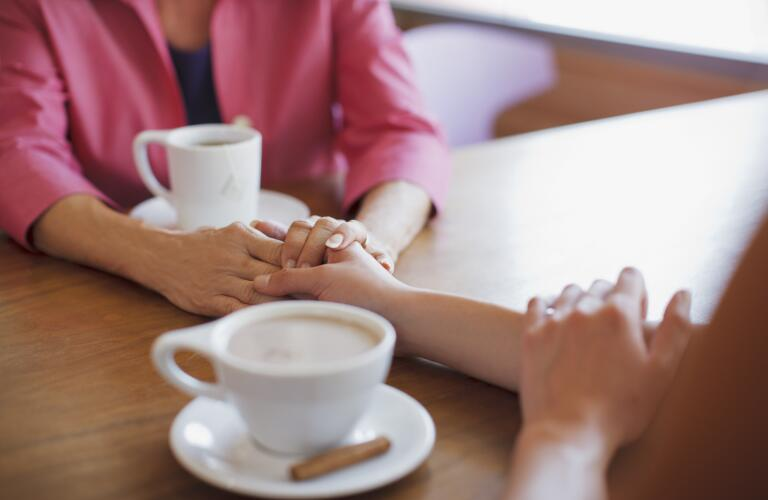 female friends holding hands across table with coffee