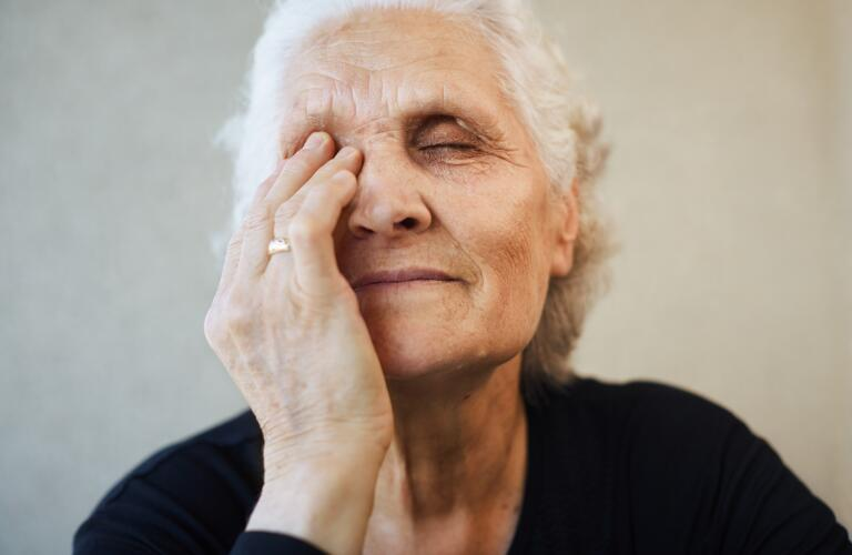 senior woman with one hand over eye