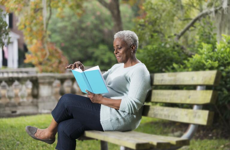 senior-african-american-woman-sitting-on-bench-reading