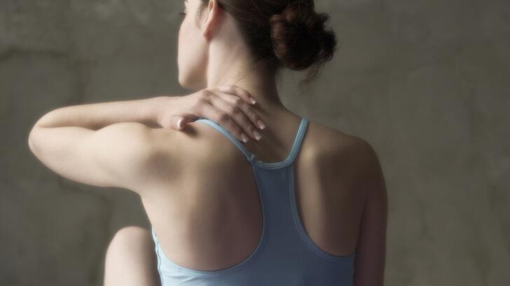 woman touching upper back