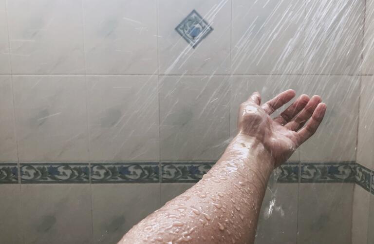 water spraying on hand in shower