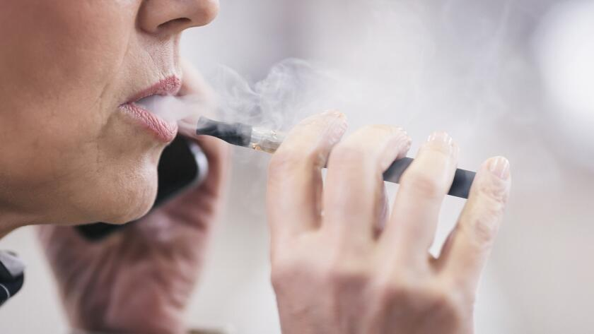 closeup of senior Caucasian woman vaping with electronic cigarette