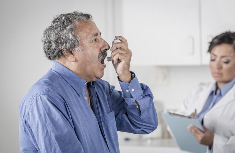 senior man in doctor's office using inhaler