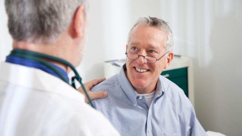 Male doctor with male patient with hand on shoulder