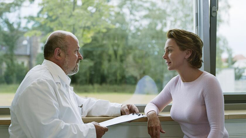 female-patient-talking-with-male-doctor