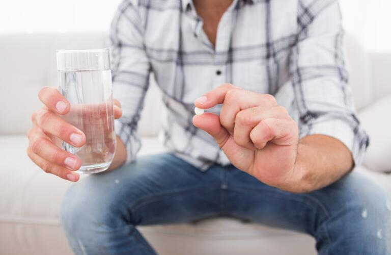 man-sitting-on-couch-holding-glass-of-water-and-pill
