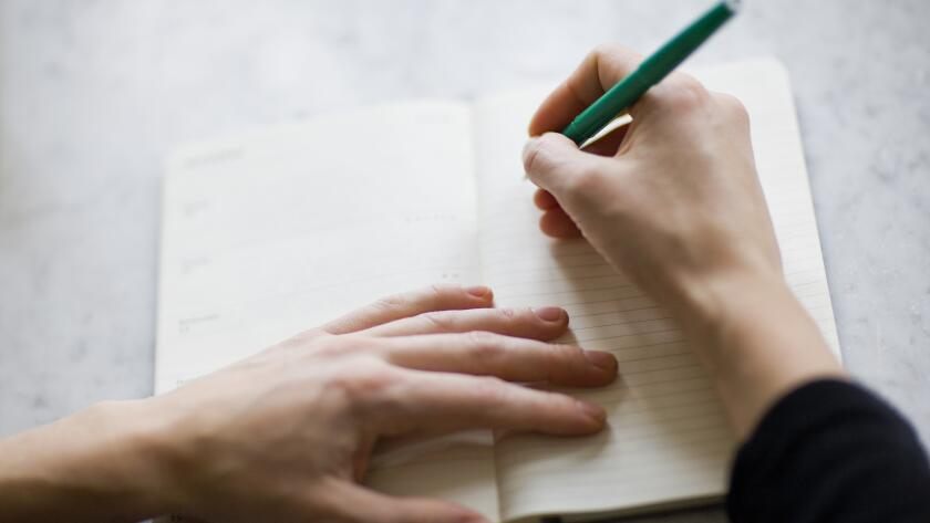 closeup of woman's hands making list in journal on table