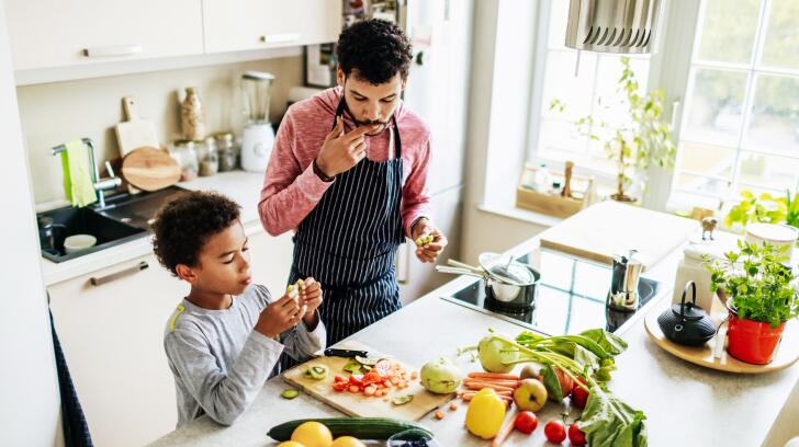 African American father and young son chopping fruits and vegetables in kitchen