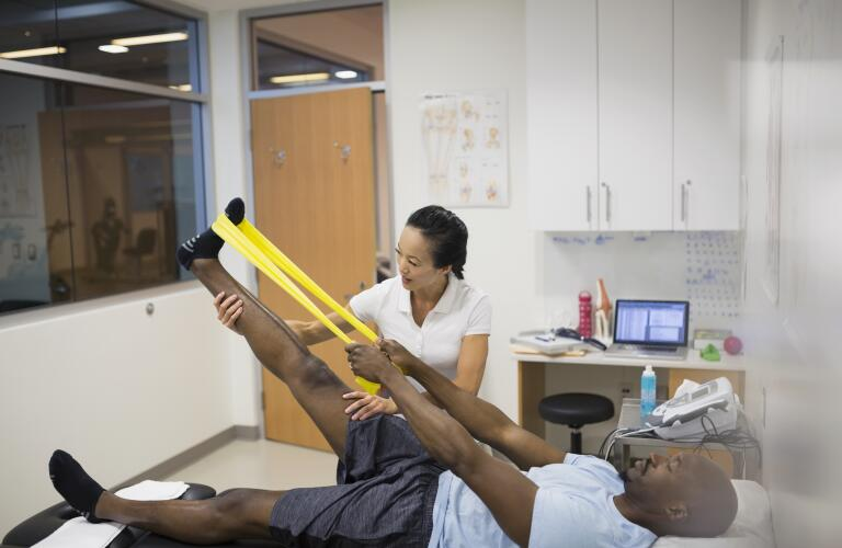 Male African American patient using stretch band on leg in physical therapy with female Asian American therapist