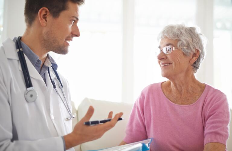 smiling-senior-woman-chatting-with-her-GP-during-an-appointment