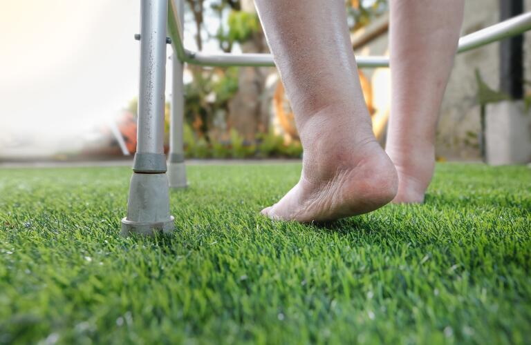 Close-up of unseen Caucasian woman's feet swollen with edema walking on grass with walker