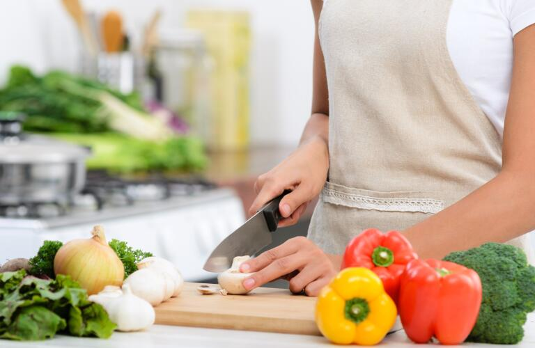 Close up of hands slicing vegetables with knife