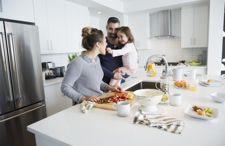Young Caucasian girl with parents in kitchen as mother chops strawberries