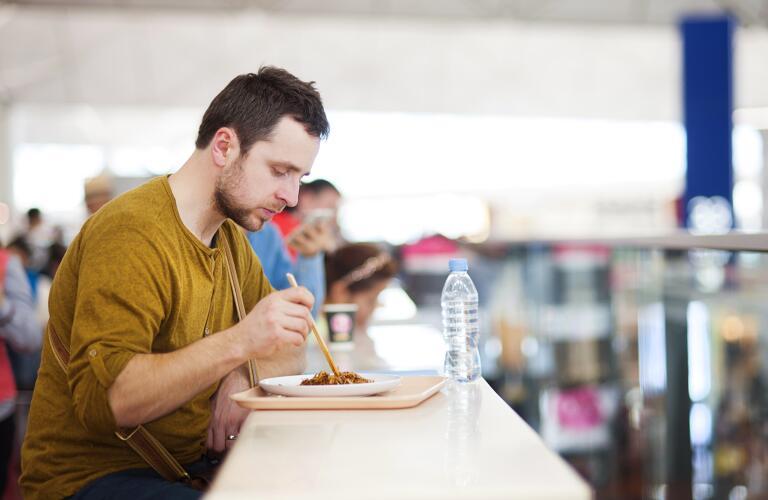 guy eating at airport