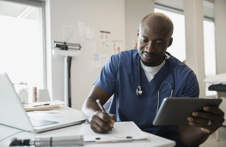 Doctor in scrubs with digital tablet and clipboard