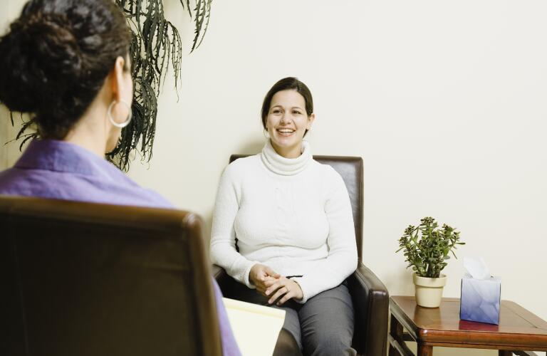 Young female patient talks to doctor or therapist