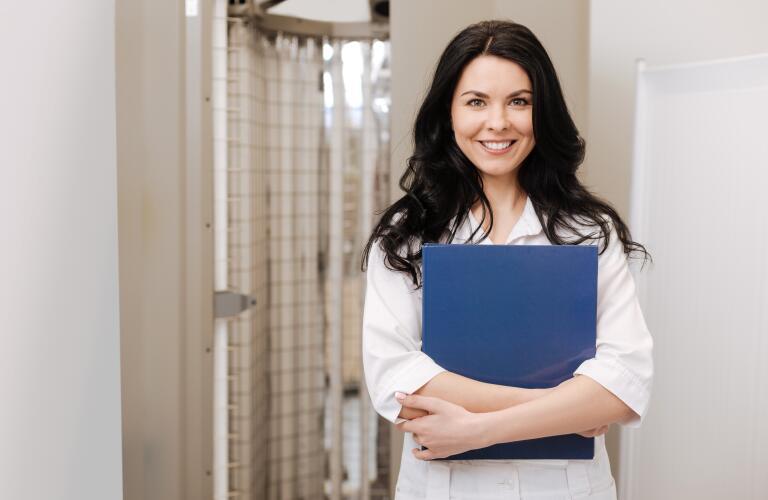 smiling female dermatologist holding files