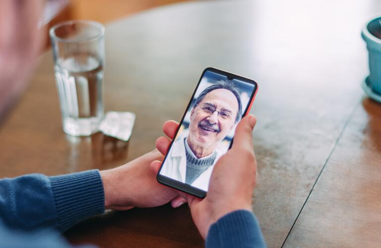 closeup of hands holding smartphone during telehealth appointment on dining table next to glass of water