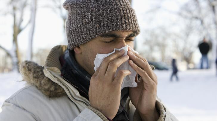 Young Caucasian man in winter coat and hat outside sneezing in cold snowy weather