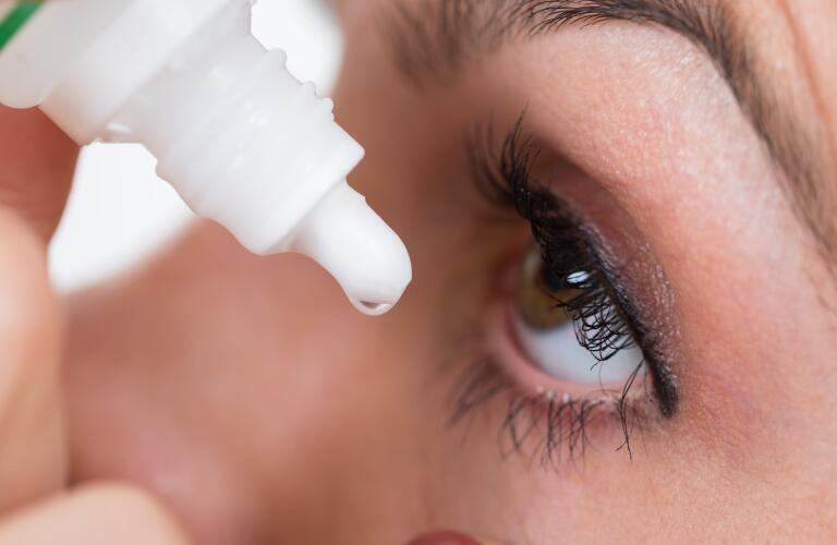 close up of woman putting eye drops into eye