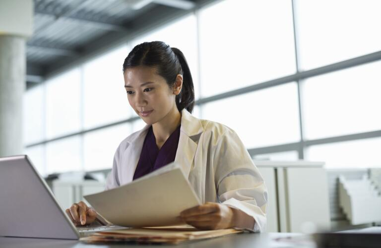 Young Asian American female doctor looking at laptop holding papers