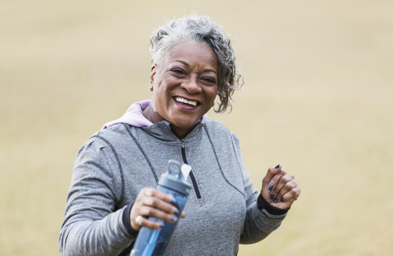 senior woman smiling with water bottle