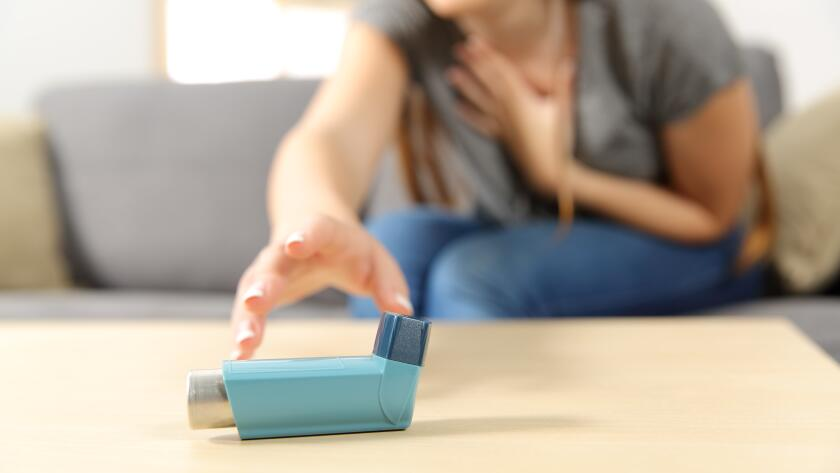 young woman reaching desperately for asthma inhaler
