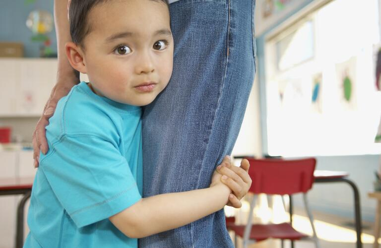 Shy young boy holding onto mother's leg